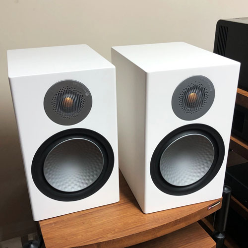 Two Monitor Audio Silver speakers on the table